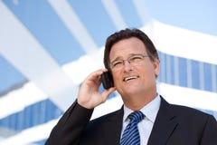 De zakenman glimlacht aangezien hij op Zijn Telefoon van de Cel spreekt Stock Fotografie
