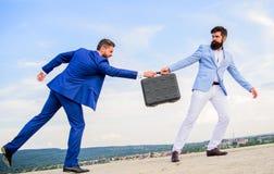 De zakenman haalt aktentas van partner weg Fraude en afpersingsconcept De overdrachtaktentas van mensenkostuums stock foto