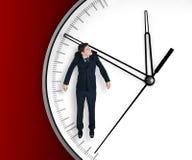 De zakenman hangt op een pijl van klok Stock Fotografie