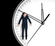 De zakenman hangt op een pijl van klok Stock Foto