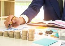 De zakenman heeft een pen in zijn rechtse analyse van grafiekgegevens, O Stock Foto