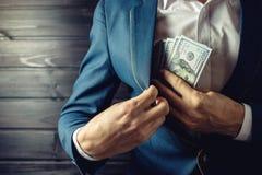 De zakenman, het lid of de ambtenaar zetten een steekpenning in zijn zak Stock Foto