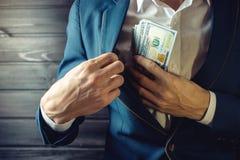 De zakenman, het lid of de ambtenaar zetten een steekpenning in zijn zak Stock Foto's