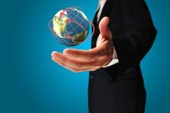 De zakenman houdt Aarde in een hand Royalty-vrije Stock Foto's