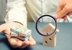 De zakenman houdt dollars in handen dichtbij blokhuis De investeringsconcept van onroerende goederen hypotheek Lening voor huisve royalty-vrije stock foto