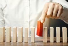 De zakenman houdt een houten blok in zijn handen Het concept personeelsselectie en beheer binnen het team Ontslag en royalty-vrije stock afbeeldingen