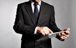 De zakenman houdt een lijstpc Stock Afbeelding