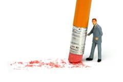 De zakenman houdt een potlood en wist een fout royalty-vrije stock afbeelding