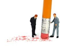 De zakenman houdt een potlood en wist een fout Stock Foto
