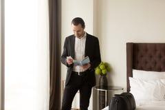 De zakenman houdt gidsbrochure en roept taxi of bediening op de kamer stock fotografie