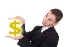 De zakenman houdt gouden de dollarteken van de V.S. Stock Afbeelding