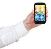 De zakenman houdt handphone met Kerstmisstilleven Stock Foto