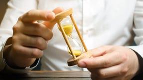 De zakenman houdt klok in handen Concept besparingstijd en geld Vector moderne illustratie in vlakke stijl met de mannelijke chro stock fotografie