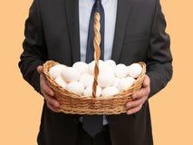 De zakenman houdt mand met eieren stock fotografie