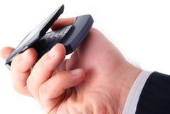 De zakenman houdt mobiele telefoon Stock Foto's