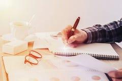 De zakenman iets op notitieboekjedocument schrijven, en het document die van het bedrijfsfinanciënrapport vertroebelden op lijst, Stock Foto