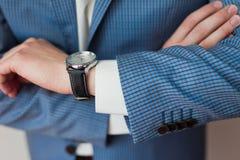 De zakenman kijkt de tijd op zijn polshorloge Royalty-vrije Stock Afbeeldingen