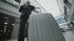 De zakenman kijkt op kaartje en spreekt op telefoon in de luchthaven stock footage