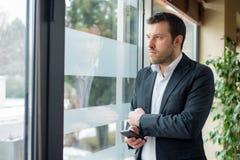 De zakenman kijkt trog het venster royalty-vrije stock afbeelding