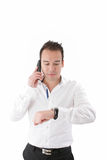 De zakenman kijkt zijn horloge stock fotografie