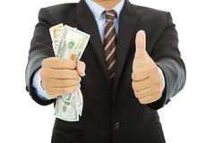 De zakenman klemt omhoog ons dicht dollars en duim Royalty-vrije Stock Afbeeldingen