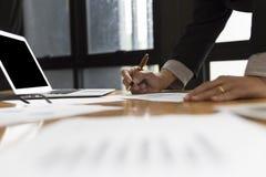 De zakenman in kostuum analyseert marktanalyse bedrijfsgrafiek met Stock Afbeeldingen