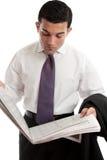 De zakenman leest aandeelprijzen in krant stock afbeelding
