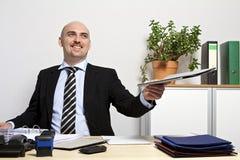 De zakenman legt smilingly een omslag voor Stock Afbeeldingen