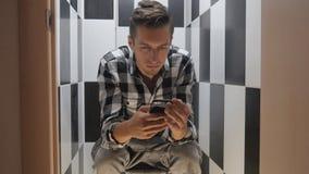 De zakenman let op het nieuws op de telefoonzitting op het toilet