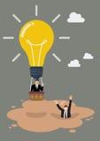 De zakenman in lightbulbballon krijgt vanaf drijfzand Stock Afbeeldingen