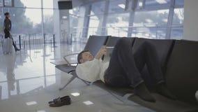 De zakenman ligt op de zetels bij de luchthaven het wachten zaal en het gebruiken van tablet stock video