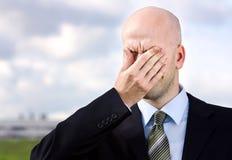De zakenman lijdt aan een hoofdpijn stock foto
