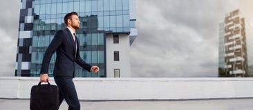 De zakenman loopt met een zak op de stad royalty-vrije stock fotografie