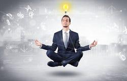 De zakenman mediteert met verlichtingsconcept stock afbeeldingen