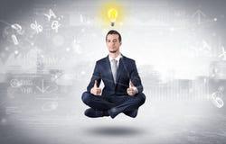 De zakenman mediteert met verlichtingsconcept stock foto