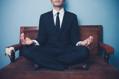De zakenman mediteert op bank Stock Foto