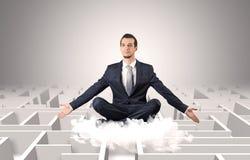 De zakenman mediteert op een wolk met labyrintconcept stock foto