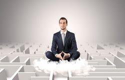 De zakenman mediteert op een wolk met labyrintconcept stock afbeelding