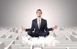 De zakenman mediteert op een wolk met labyrintconcept stock foto's