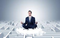 De zakenman mediteert op een wolk met labyrintconcept royalty-vrije stock afbeeldingen