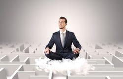 De zakenman mediteert op een wolk met labyrintconcept stock fotografie