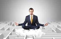 De zakenman mediteert op een wolk met labyrintconcept royalty-vrije stock foto