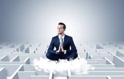 De zakenman mediteert op een wolk met labyrintconcept stock afbeeldingen