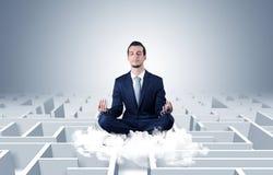 De zakenman mediteert op een wolk met labyrintconcept royalty-vrije stock foto's