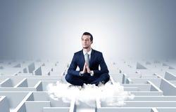 De zakenman mediteert op een wolk met labyrintconcept royalty-vrije stock afbeelding