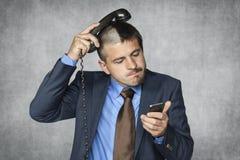 De zakenman met een grappig kapsel kan geen telefoon behandelen royalty-vrije stock foto's