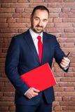 De zakenman met een rood pak biedt aan om een pen te nemen royalty-vrije stock fotografie