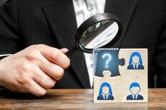 De zakenman met een vergrootglas onderzoekt het ontbrekende deel van het raadselteam Zoeken, rekruteringspersoneel, hurende leide stock fotografie