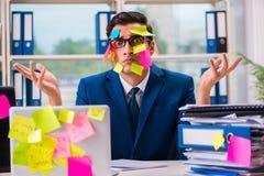 De zakenman met herinneringsnota's in multitasking concept royalty-vrije stock afbeelding