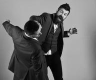 De zakenman met woedend gezicht raakt en slaat tegenstander royalty-vrije stock foto